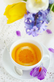 cup of tea with lemon and spring flowers close up