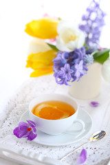 cup of tea with lemon and spring flowers, soft focus