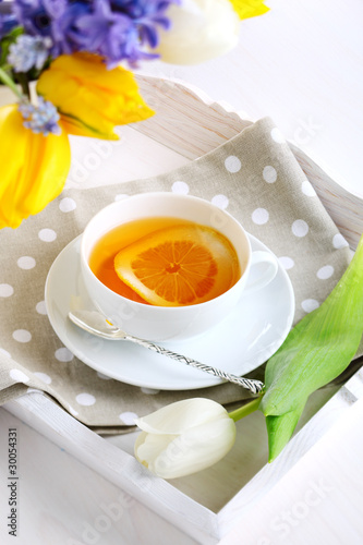cup of tea with lemon on white tray with spring flowers