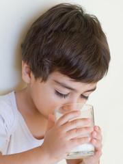 bambino che beve bicchiere di latte