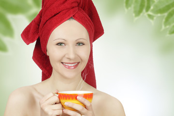 Young woman with towel drinking tea