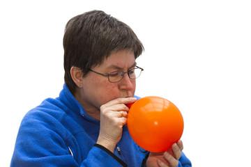 Inflating an orange balloon