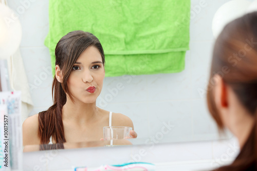 Woman using mouthwash