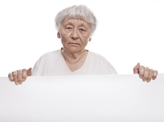 Serious senior woman holding a blank sign