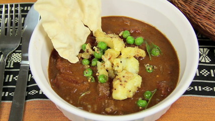 Potato and peas put into an Indian curry and a pappadum.
