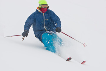 Young man skiing in snowstorm