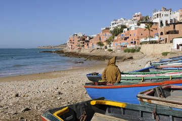 Fisherman wearing traditional burnous sitting on a fishing boat