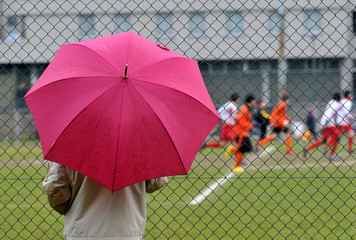 Parent observes young players in the rain