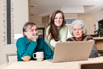 Teenage girl with grandparents using laptop