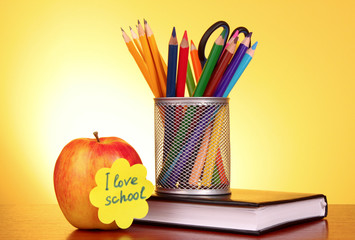 "Stationery and apple with ""I love school"" on yellow background"
