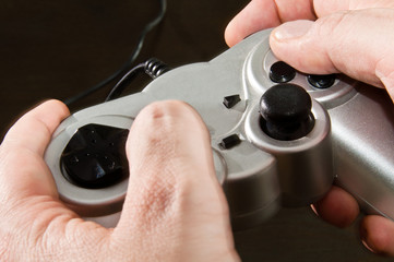 hands holding silver gamepad of video game