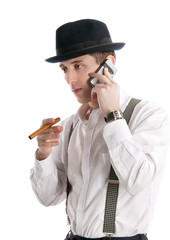 young man talks by a mobile phone and holds cigar.