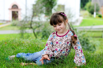Adorable little girl in colorful clothes sits on grass