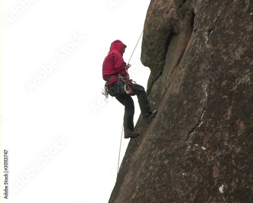 Climber on steep cliff.