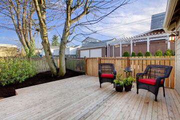 Deck with two chairs and fenced yard near home exterior shot.