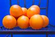 Orangen auf einem Eisenstuhl vor blauer Wand