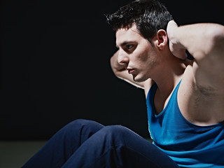 man doing series of sit-ups on black background
