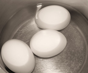 Three eggs in pot of water ready to boil