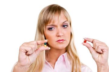 junge frau schaut nachdenklich auf zwei tabletten