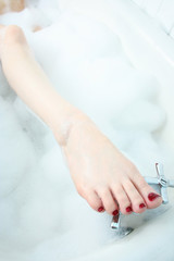 Close up of woman's foot in bubble bath