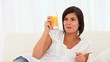 Attractive bronw-haired woman drinking a glass of orange juice