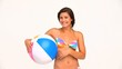 Brunette woman in swimsuit playing with a beach ball