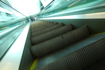 abstract steps of green escalator with persons on the top