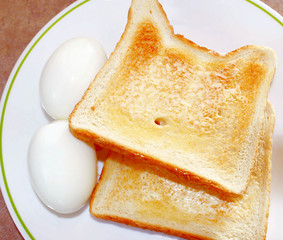 Two hard-boiled eggs with buttered toast