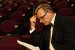 Male symphony conductor studying his music score