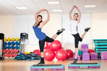 Two woman doing stretching exercise at gym