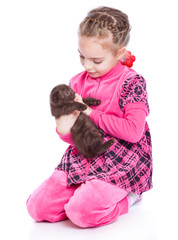 a smiling girl is playing with a kitten