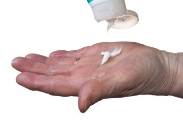 Elderly woman healing dry hands with hand lotion