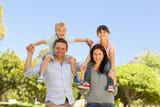 Fototapety Parents giving  children a piggyback
