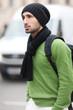 Mann mit Rucksack und grünem Pulli