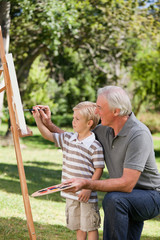 Happy Grandfather and his grandson painting in the garden