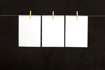 Blank sheets of paper, hanging from a wire