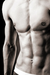 Ideal muscular & tanned male body. Close-up torso.