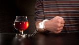 Hand locked to glass of alcohol poster