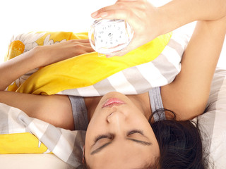 tired teenage girl lying in bed looking at the clock