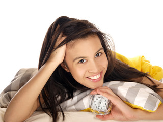 smiling teenage girl lying in bed holding a clock