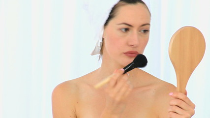 Cute bunette lady putting make-up on
