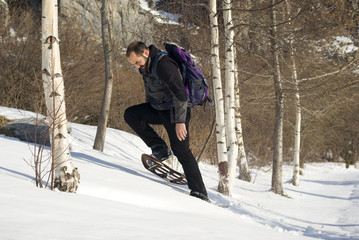 Man in snow shoes in a winter forest