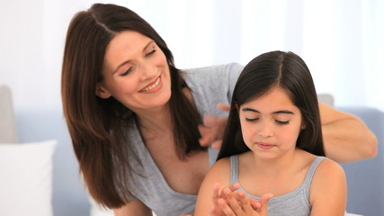 Brunette mother fixing hair of her daughter
