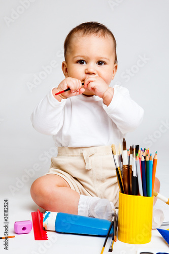 Kid playing with paints and pencils