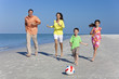 Mother, Father and Children Family Running With Ball on Beach