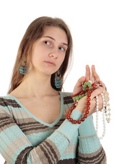 The girl with blue earrings holds a colorful beads