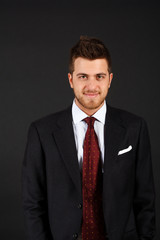 Handsome smiling businessman isolated on dark background