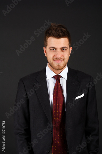 Handsome smiling businessman isolated on dark background