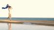 Woman with waving sarong walking on the seashore, slow motion