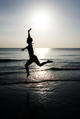 Woman leaping on the beach at sunset